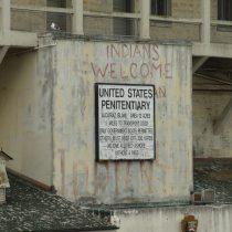 Napisy nawiązują do okupacji tereny przez rdzenną ludność amerykańską, co miało miejsce po likwidacji więzienia w latach 60'.