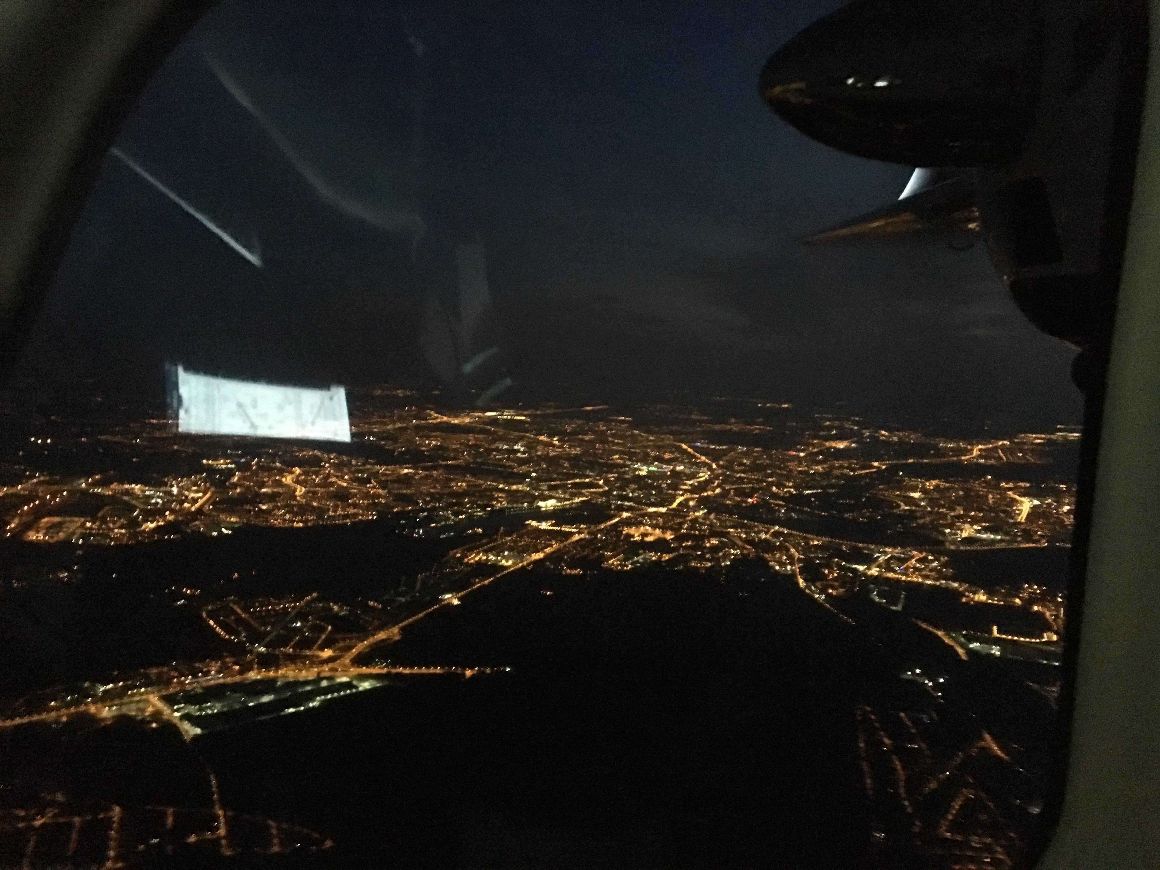 Poznań nocą. Na szybie odbija się karta podejścia.