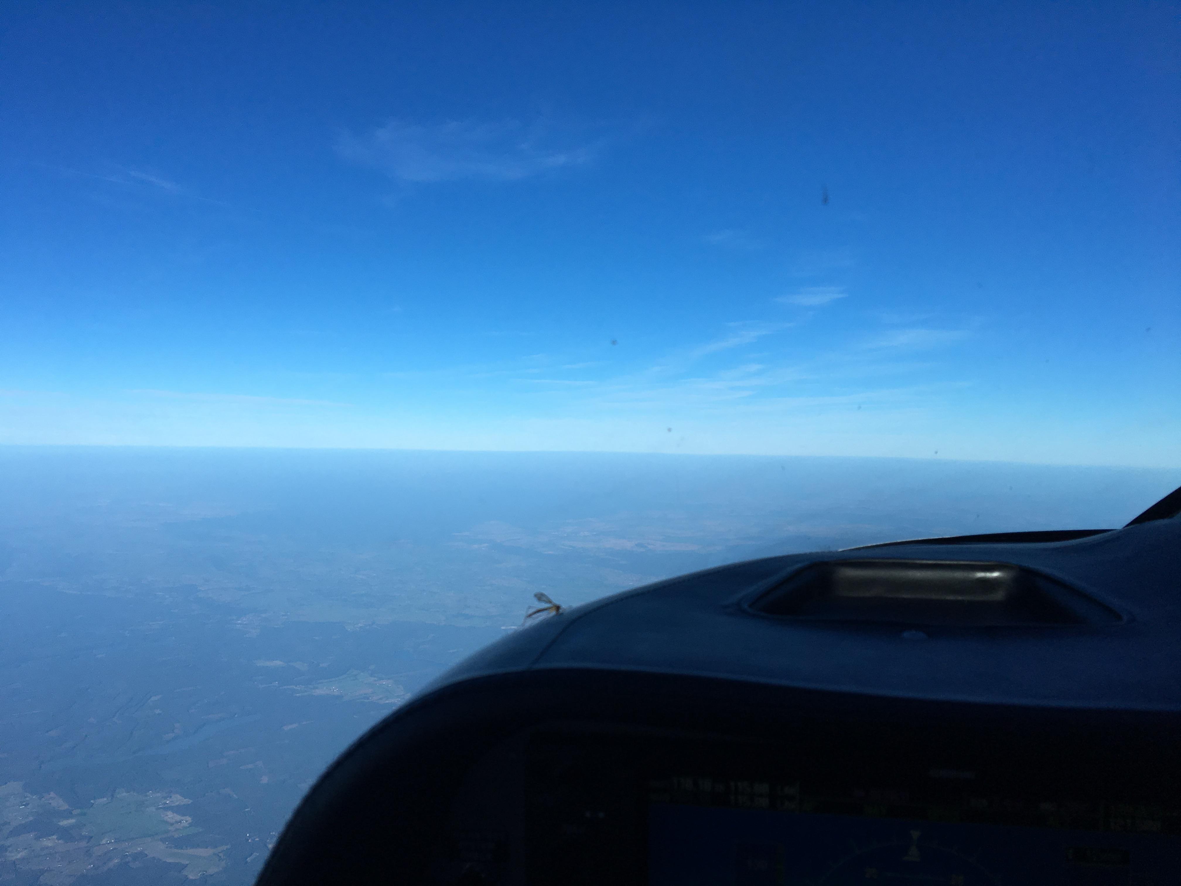 Zdjęcie przedstawia widok przez przednią szybę samolotu wykonującego przelot na FL120 w bezchmurny dzień.