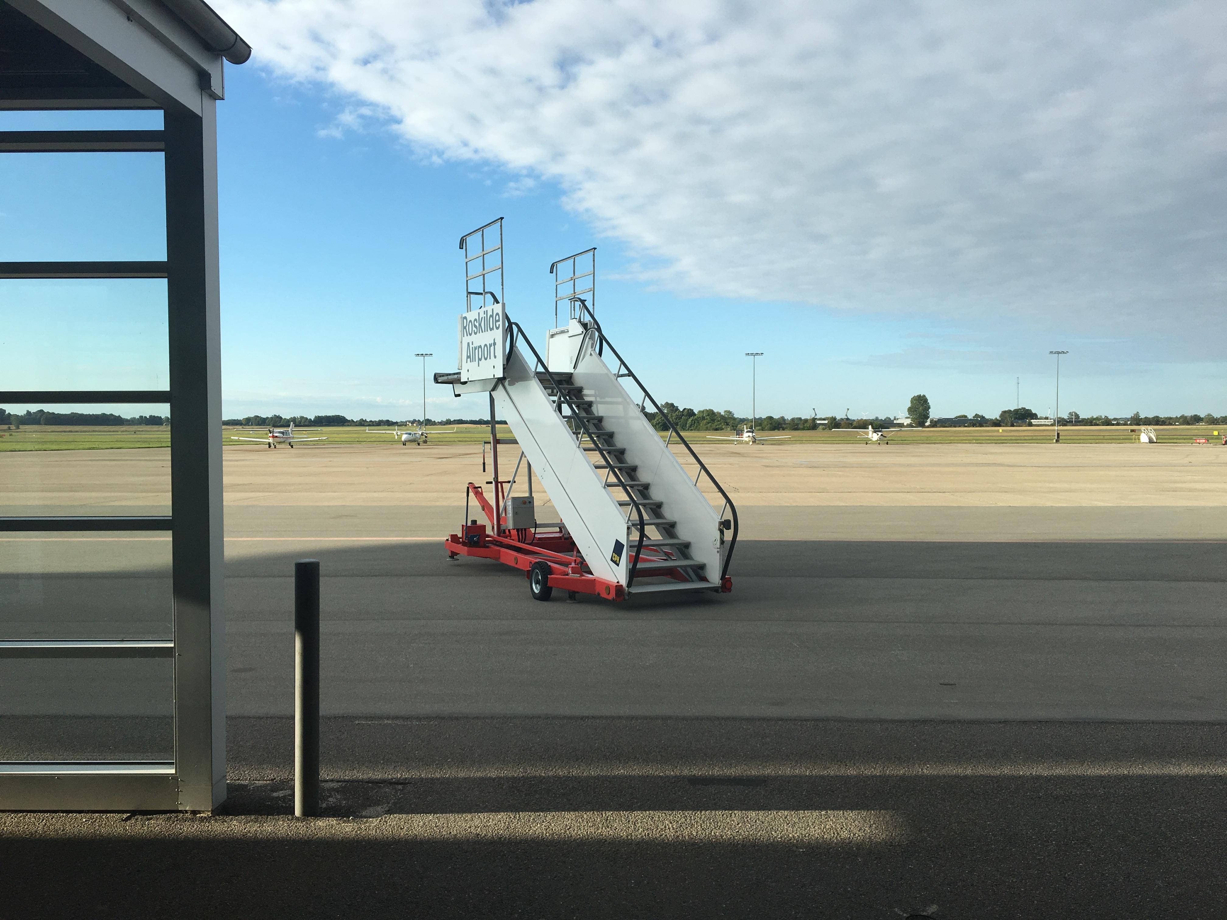 Zdjęcie przedstawia płytę postojową lotniska Roskilde (EKRK). Na pierwszym planie są schody.